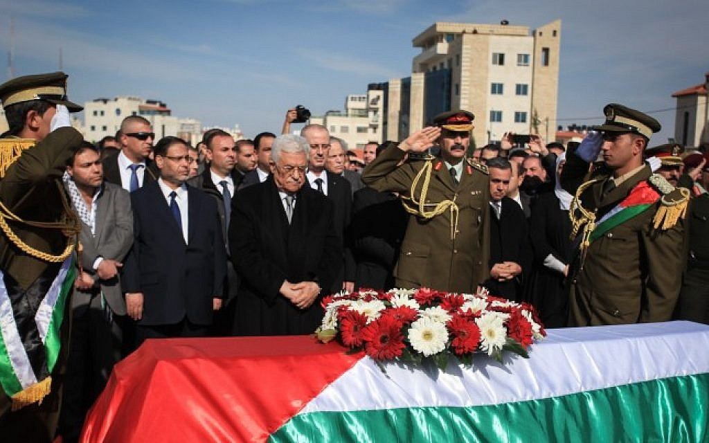 Palestinian Authority President Mahmoud Abbas stands by the coffin of senior Palestinian official Ziad Abu Ein during his funeral in the West Bank city of Ramallah, on December 11, 2014. (photo credit: STR/Flash90)