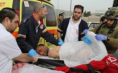 Medics evacuate a Palestinian man after he was shot following an acid attack on an Israeli family of five in Gush Etzion on December 12, 2014. (Photo credit: Gershon Elinson/Flash90)
