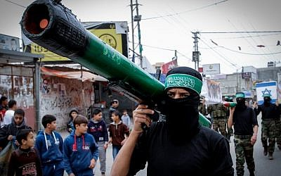Masked members from the Izz ad-Din al-Qassam Brigades carry a model of a rocket during a rally to commemorate the 27th anniversary of the Islamist movement Hamas at the Nuseirat refugee camp in the Central Gaza Strip, December 12, 2014 (Abed Rahim Khatib/Flash90)