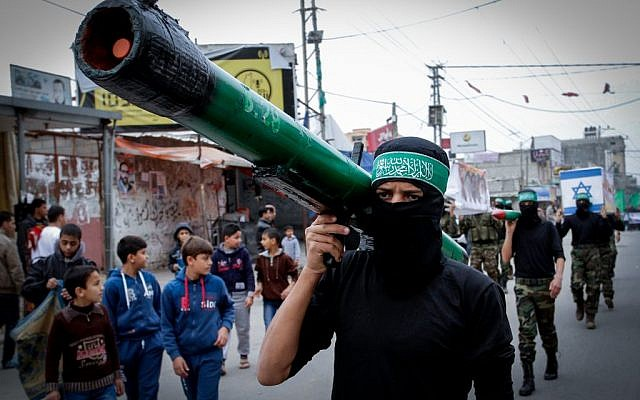 A masked Hamas member carries a model of a rocket during a rally in the Nuseirat refugee camp in the central Gaza Strip on December 12, 2014 (photo credit: Abed Rahim Khatib/Flash90)