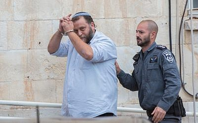 Lehava chairman Benzi Gopshtain is brought to the Jerusalem's Magistrates Court in Jerusalem on December 16, 2014. (Yonatan Sindel/Flash90)
