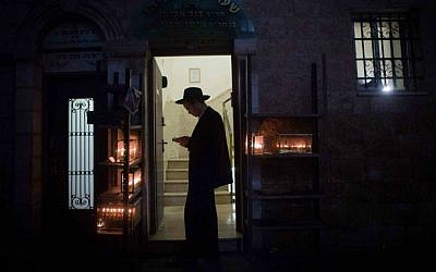 An ultra-Orthodox Jewish man lights candles for the Jewish holiday of Hanukkah in the poor, ultra-Orthodox Jerusalem neighborhood of Mea Shearim, December 23, 2014. (Yonatan Sindel/Flash90)