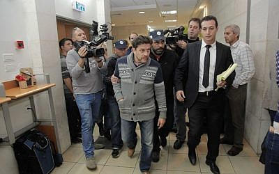 Yisrael Beytenu chief of staff David Godowsky is brought to the Rishon Lezion Magistrate's Court on December 24, 2014. (photo credit: FLASH90)