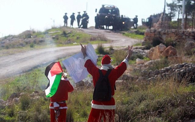Palestinian protesters wearing Santa Claus costumes wave during a protest against Israel's security barrier outside the West Bank village of Bil'in, near Ramallah, Friday, December 26, 2014 (Photo credit: STR/Flash90)