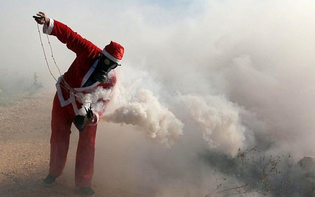 A Palestinian protester wearing a Santa Claus costume holds a tear gas canister during a protest against Israel's security barrier outside the West Bank village of Bil'in, near Ramallah, Friday, December 26, 2014 (photo credit: STR/Flash90)