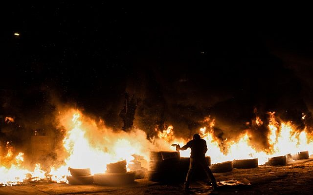 Illustrative: Givat Amal residents burn tires on December 29, 2014. (Amir Levi/Flash90)