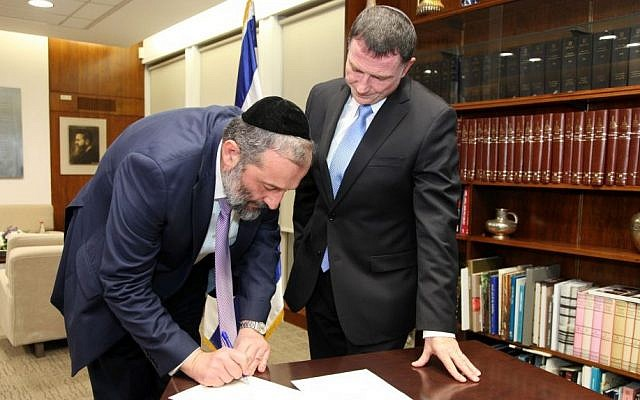 Shas party leader Aryeh Deri signs a letter resigning from the Knesset, as Speaker Yuli Edelstein looks on, December 30, 2014. (Photo credit: Isaac Harari/Knesset Spokesperson)