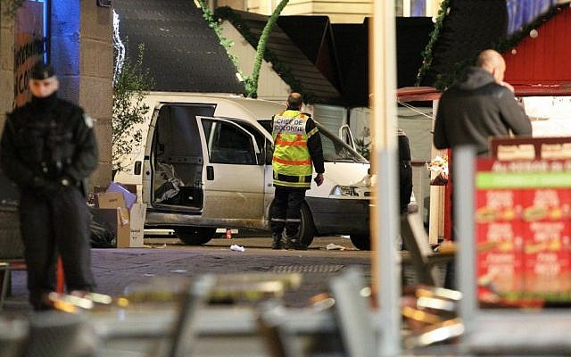 A police officer guards the van that crashed into a French Christmas market in Nantes, western France, Monday, Dec. 22, 2014. (Photo credit: AP/Laetitia Notarianni)