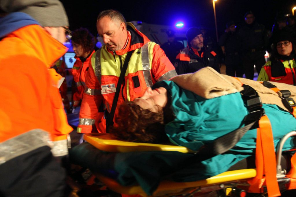 A woman is carried by paramedics as passengers of the ferry that caught fire in the channel between Italy and Albania are transported to the town of Otranto, near Lecce, southern Italy, Sunday, Dec. 28, 2014. (photo credit: AP Photo/Ivan Tortorella)