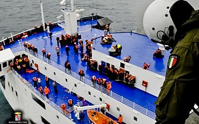 In this image released by the Italian Navy, passengers and crew are seen on the deck of the Italian-flagged ferry Norman Atlantic as it is approached by a rescue helicopter after it caught fire in the Adriatic Sea, Sunday, Dec. 28, 2014. (photo credit: AP/Italian Navy)