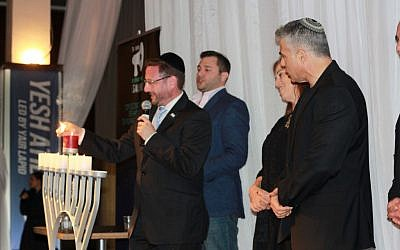 Yesh Atid MKs Dov Lipman, Ruth Calderon, and Yair Lapid light the sixth candle of Hanukkah at an event for Anglo olim on Sunday, November 21, 2014. (photo credit: Courtesy/Deborah Danan)