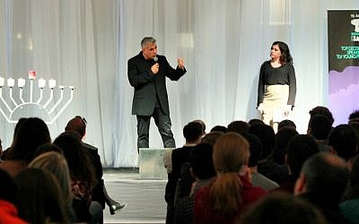 Yair Lapid of the Yesh Atid party speaks with Tel Aviv International Salon host Natalie Solomon and about 300 young English-speaking olim in Tel Aviv, December 21, 2014. (Courtesy Deborah Danan)