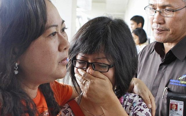 A relative of Air Asia flight QZ8501 passengers weep as she waits for the latest news on the missing jetliner at Juanda International Airport in Surabaya, East Java, Indonesia on Sunday, Dec. 28, 2014. (photo credit: AP/Trisnadi)