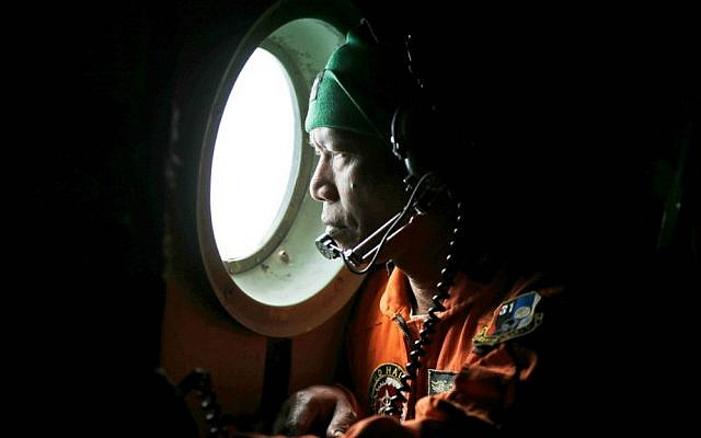 A crew of an Indonesian Air Force C-130 airplane of the 31st Air Squadron looks out of the window during a search operation for the missing AirAsia flight 8501 jetliner over the waters of Karimata Strait in Indonesia, Monday, Dec. 29, 2014. (AP Photo/Dita Alangkara)