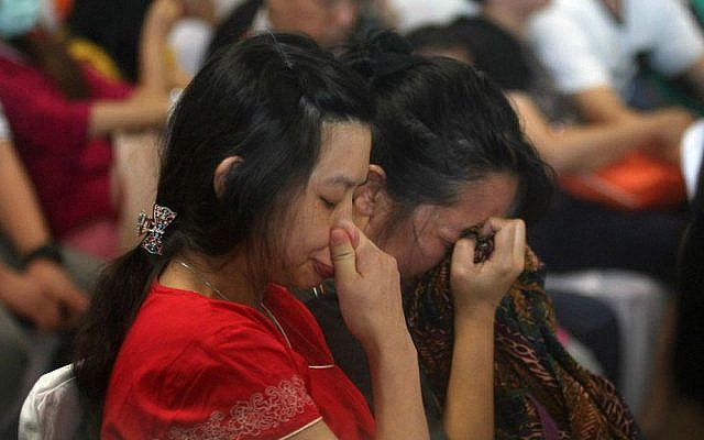 Relatives and next-of-kin of passengers on the AirAsia flight QZ8501 wait, some in tears while others in prayer, for the latest news on the search of the missing jetliner at Juanda International Airport in Surabaya, East Java, Indonesia, Monday, Dec. 29, 2014. (AP Photo/Trisnadi Marjan)