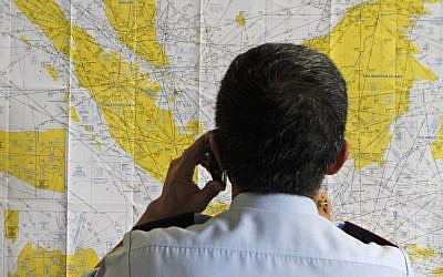 An airport official checks a map of Indonesia at the crisis center set up by local authority for the missing AirAsia flight QZ8501, at Juanda International Airport in Surabaya, East Java, Indonesia, Sunday, Dec. 28, 2014.  (photo credit: AP/Trisnadi)