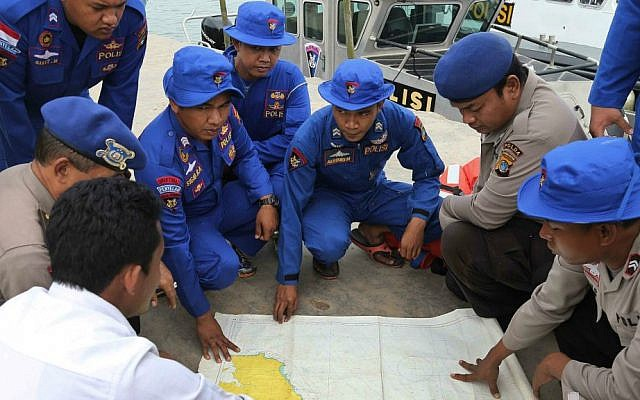 Members of Indonesia's Marine Police hold a briefing on board a search and rescue craft prior to their heading out to sea to search for the missing AirAsia flight QZ8501, at Pangkal Pinang port in Sumatra Island, Monday Dec. 29, 2014 in Indonesia. (AP Photo/Tatan Syuflana)