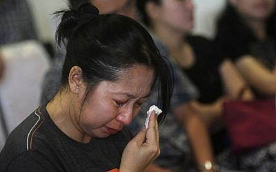A relative of a passenger on the AirAsia flight QZ8501 wipes tears as she awaits the latest news on the search of the missing jetliner at Juanda International Airport in Surabaya, East Java, Indonesia, Monday, Dec. 29, 2014. (photo credit: AP Photo/Trisnadi Marjan)