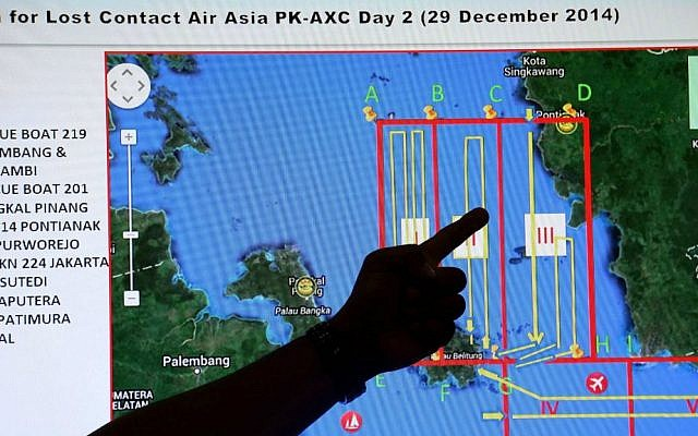 A member of the Indonesian National Search and Rescue Agency (BASARNAS) points to a map of a search area during a briefing prior to a search and rescue operation of the missing AirAsia flight QZ8501, at Pangkal Pinang command post in Sumatra Island, Monday, Dec. 29, 2014 in Indonesia. (AP Photo/Tatan Syuflana)