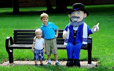 The Hoffman boys pose next to their father's creation, Mensch on a Bench. (courtesy)