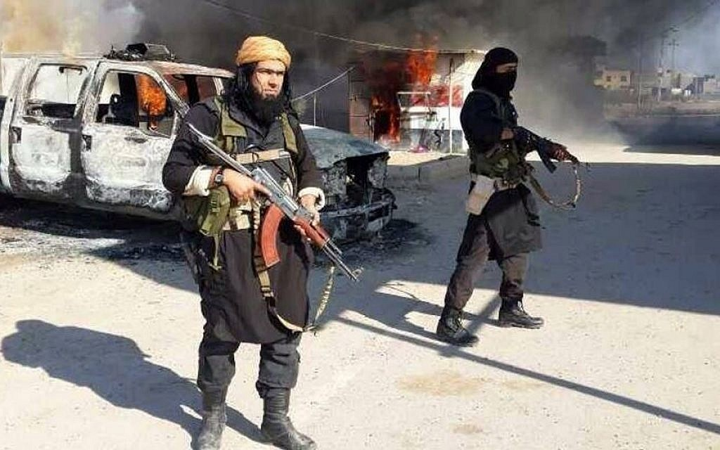 This undated file image posted on a militant website on January 4, 2014, which is consistent with other AP reporting, shows Shakir Waheib, a senior member of the Islamic State of Iraq and the Levant (ISIL), now called the Islamic State group, left, next to a burning police vehicle in Iraq's Anbar Province. (Photo credit: AP via militant website, File)