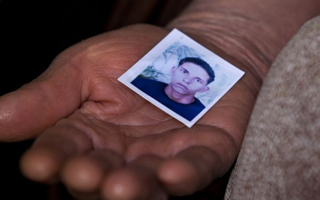 The mother of Mohamed Bouazizi, the local fruit vendor who set himself on fire December 17, 2010, holds a picture of him, in the town of Sidi Bouzid, Tunisia, March 8, 2011. (AP/Giorgos Moutafis, File)