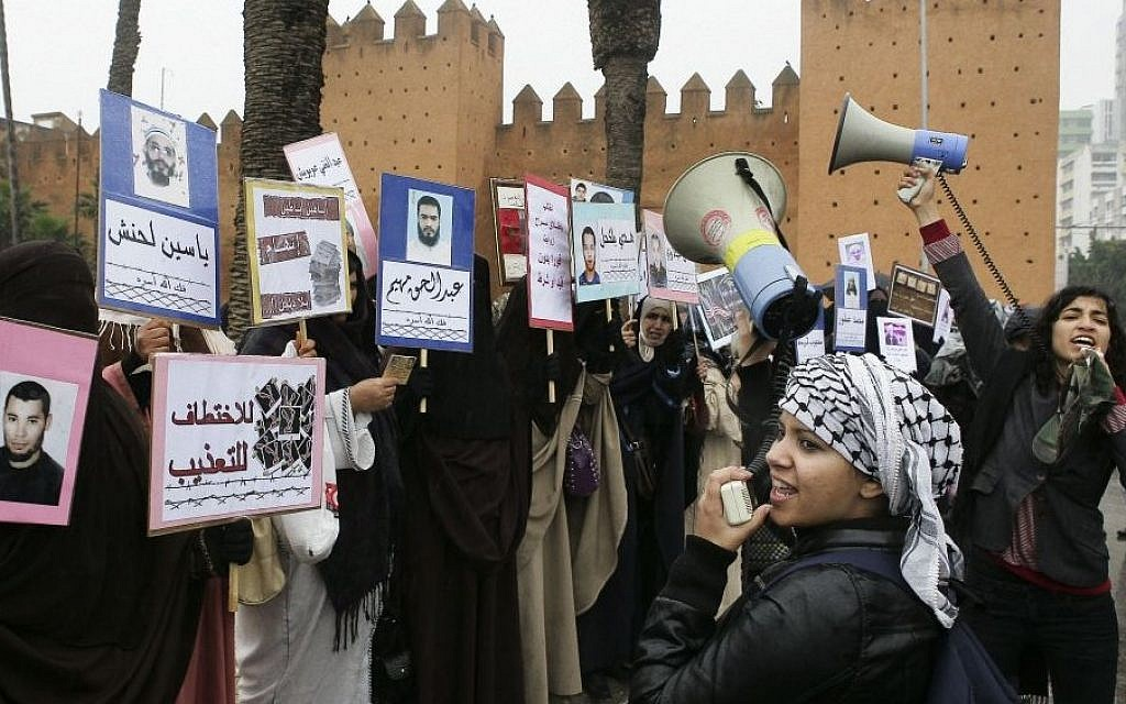 In this February 20, 2014 file photo, two women activists shout slogan against the Moroccan government near veiled women holding placards of jailed relatives during a protest in Rabat. Every one of the countries whose leader was toppled _ Tunisia, Egypt, Libya and Yemen _ had been run by authoritarian civilians backed by military power. So is Syria, where war rages still. The monarchies, from Morocco to Jordan and Saudi Arabia and the neighboring Emirates, Bahrain, Qatar and Kuwait, were barely touched. (Photo credit: AP/Abdeljalil Bounhar, File)