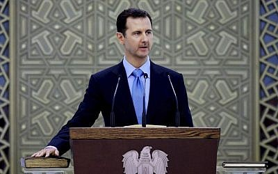 In this Wednesday, July 16, 2014 file photo released by the Syrian official news agency SANA, Syria's President Bashar Assad is sworn for his third, seven-year term, in Damascus, Syria (AP/SANA, File)