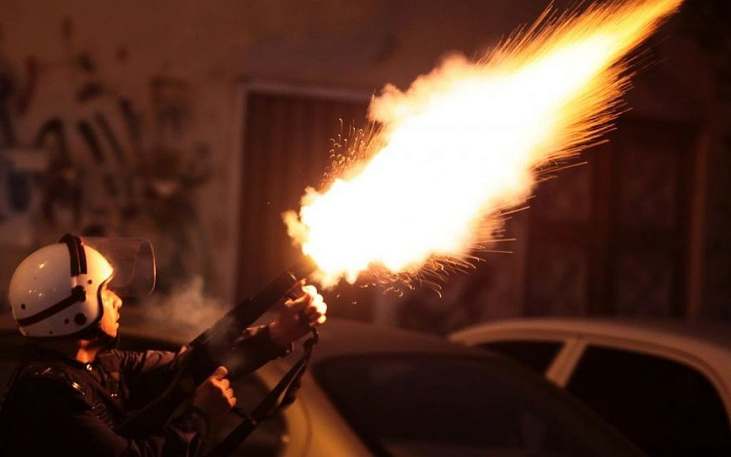 In this September 13, 2013 file photo, a riot policeman fires tear gas to disperse Bahraini anti-government protesters during a planned march, called by several opposition groups but denied authorization by police in Mussala, Bahrain. (Photo credit:AP/Hasan Jamali, File)