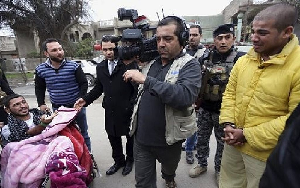 "In this photo taken Tuesday, Dec. 16, 2014, Haider Ali Motar, right, performs a scene from ""In the Grip of the Law,"" a reality show produced by Iraqi state TV. Motar was convicted about a month ago for helping to carry out a string of Baghdad car bombings on behalf of the Islamic State extremist group. (AP Photo/Hadi Mizban)"
