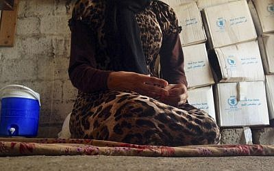 Illustrative: A 15-year-old Yazidi girl captured by the Islamic State group and forcibly married to a militant in Syria sits on the floor of a one-room house she now shares with her family after escaping, October 8, 2014. (AP/Dalton Bennett, File)