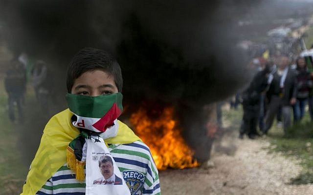A Palestinian youth covers his face with a scarf with an image of senior PA official Ziad Abu Ein in the West Bank village of Turmus Aya near Ramallah, Friday, December 19, 2014. (Photo credit:AP/Majdi Mohammed)