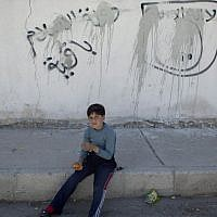 """A Jordanian boy sits on the sidewalk by painted-over graffiti depicting the flag of the Islamic State group with Arabic that reads """"their is only one God and Muhammad is his prophet, the Islamic state is staying,"""" October 29, 2014. (AP/Nasser Nasser)"""
