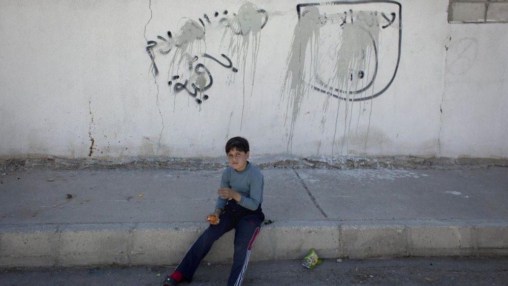 A Jordanian Boy Sits On The Sidewalk By Painted Over Graffiti Depicting The Flag Of