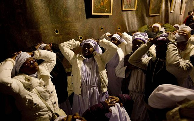Christian pilgrims from Nigeria pray inside the Grotto of the Church of the Nativity, traditionally believed by Christians to be the birthplace of Jesus Christ, in the West Bank city of Bethlehem on Christmas Eve Wednesday, Dec. 24, 2014. (photo credit: AP Photo/Majdi Mohammed)