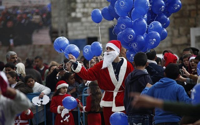 A Palestinian dressed as Santa Claus holds balloons at Manger Square, outside the Church of the Nativity, traditionally believed by Christians to be the birthplace of Jesus Christ, in the West Bank city of Bethlehem on Christmas Eve Wednesday, Dec. 24, 2014. (photo credit: AP Photo/Majdi Mohammed)