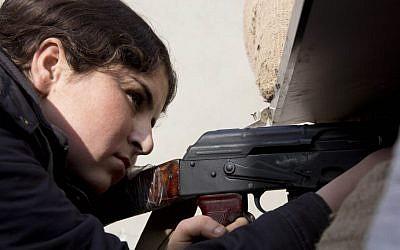 A female Kurdish fighter takes aim in Kobani, Syria, Wednesday, November 19, 2014 (photo credit: AP/Jake Simkin)
