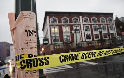 'Crime scene' tape is wrapped around a pole in front of Chabad-Lubavitch Hasidic headquarters in New York, December 9, 2014. (photo credit: AP/Mark Lennihan)