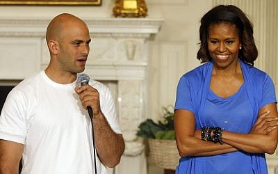 First lady Michelle Obama stands with chef Sam Kass, recently resigned White House senior policy adviser for nutrition policy, at the White House in Washington, DC,  June 12, 2104. (photo credit: AP/Charles Dharapak, File)