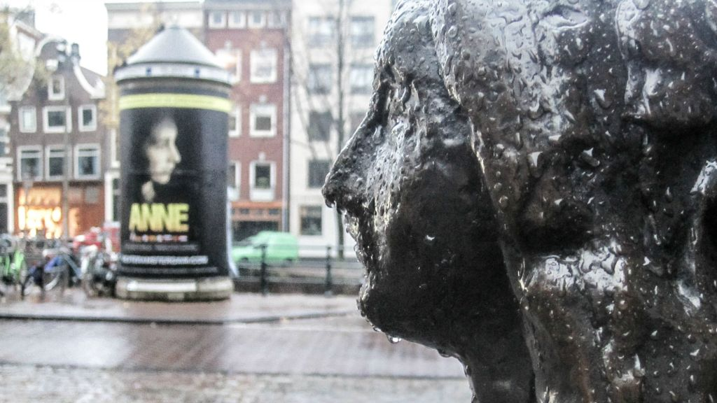 Photographed close to the Anne Frank House in Amsterdam, a statue of the diarist faces a poster for 'Anne,' the recently extended Dutch play based on Frank's writings, produced with the Anne Frank Fonds (photo credit: Matt Lebovic/The Times of Israel)