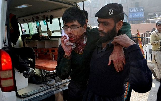 A hospital security guard helps a student injured in the shootout at a school under attack by Taliban gunmen in Peshawar, Pakistan,Tuesday, Dec. 16, 2014. (photo credit: AP/Mohammad Sajjad)
