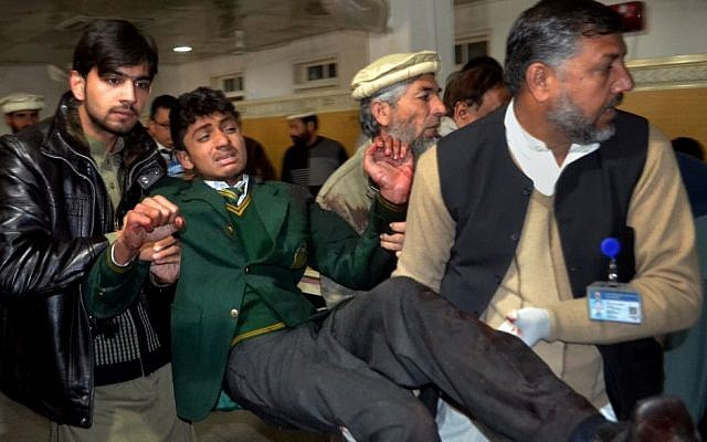 Pakistani volunteers carry a student at a local hospital after he was injured during a shootout at a school under attack by Taliban gunmen,  in Peshawar, Pakistan, Tuesday, Dec. 16, 2014. (photo credit:AP/Mohammad Sajjad)
