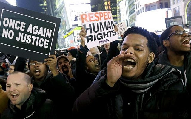 Protesters shout in Times Square after the announcement that the New York City police officer involved in the death of Eric Garner is not being indicted, December 3, 2014. (photo credit: AP/Julio Cortez)
