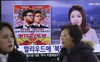 """People walk past a TV screen showing a poster of Sony Picture's """"The Interview"""" in a news report, at the Seoul Railway Station in Seoul, South Korea, Monday, Dec. 22, 2014. (Photo credit: AP/Ahn Young-joon)"""