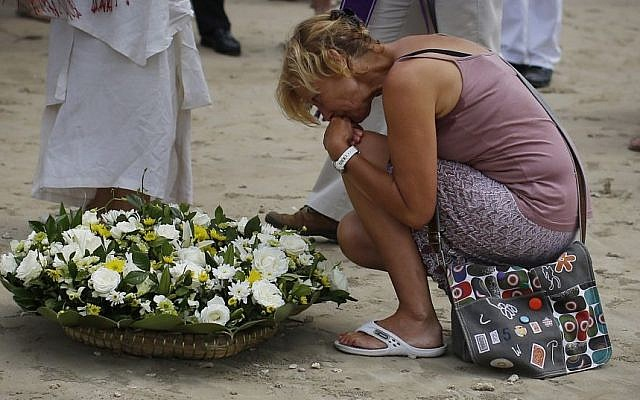 A relative of a victim from the Asian tsunami holds back her tears as she lays a white rose on the beach during a commemoration and religious ceremony for German, Austrian and Swiss victims of the Asian tsunami, in Khao Lak, Thailand, Friday, Dec. 26, 2014. (Photo credit: AP/Wong Maye-E)