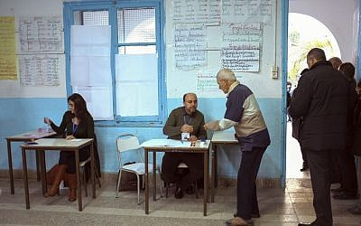 Tunisians check voters' ID prior to cast their ballots in a polling station in Tunis, Tunisia, Sunday, Dec. 21, 2014. (photo credit: AP Photo/Ilyess Osmane)