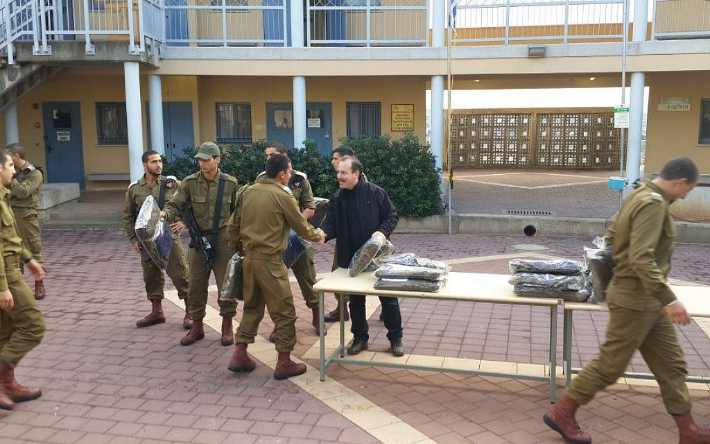 Yashar Lachayal's Leon Blankrot, in black, handing out aid packages with cold-weather gear to an all-Druze Israeli army unit, Nov. 28, 2014. (Courtesy Yashar Lachayal/JTA)