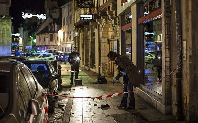 "A policewoman collects evidence on December 21, 2014 in Dijon on the site where a driver shouting ""Allahu Akbar"" (""God is great"") ploughed into a crowd injuring 11 people, two seriously, a source close to the investigation said. (photo credit: AFP PHOTO / ARNAUD FINISTRE)"