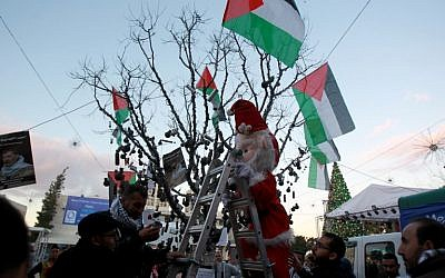 "A Palestinian dressed up as Father Christmas decorates a ""popular resistance"" Christmas tree with tear gas canisters and Palestinian flags at Manger Square, outside the Church of the Nativity, traditionally believed by Christians to be the birthplace of Jesus Christ, in the West Bank biblical city of Bethlehem, on December 23, 2014. (photo credit: AFP PHOTO / MUSA AL-SHAER)"