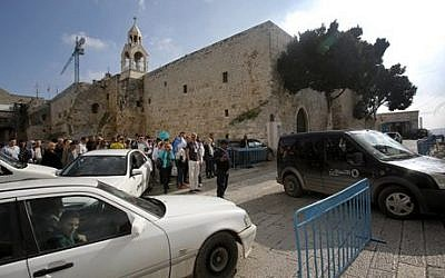 In this Sunday, Dec. 14, 2014, photo tourists walks and cars drive past the Church of the Nativity in Bethlehem, West Bank. (photo credit: AP Photo/Nasser Shiyoukhi)